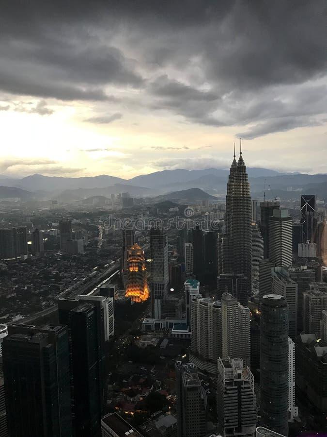 Ουρανοξύστες και πύργοι Petronas, η πρωτεύουσα της Μαλαισίας, Κουάλα Λουμπούρ, ενάντια στο σκηνικό των βουνών και του ουρανού με  στοκ εικόνες