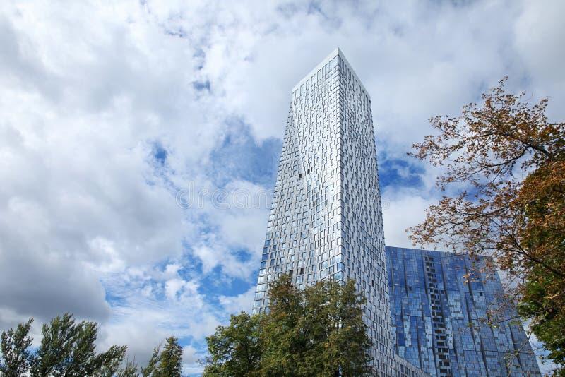 Ουρανοξύστης με τα αντανακλημένα παράθυρα ενάντια σε έναν μπλε ουρανό με τα μεγάλα σύννεφα και τα δέντρα Μόσχα 07 09 2016 στοκ εικόνες με δικαίωμα ελεύθερης χρήσης