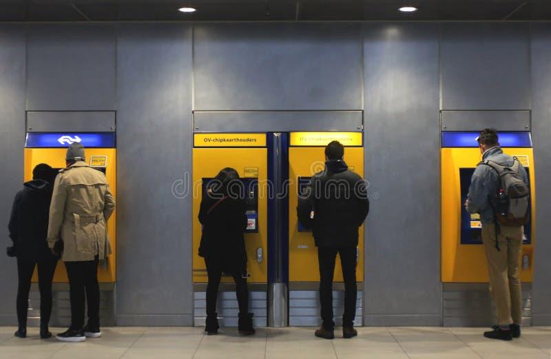 Ουτρέχτη, οι Κάτω Χώρες, στις 15 Φεβρουαρίου 2019: άνθρωποι μπροστά από τη μηχανή εισιτηρίων για να πληρώσει για το ταξίδι τους μ στοκ φωτογραφία