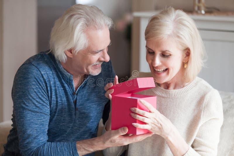 Ο αγαπώντας σύζυγος προετοιμάζεται για το κιβώτιο δώρων συζύγων στοκ φωτογραφίες με δικαίωμα ελεύθερης χρήσης
