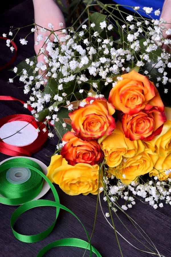 Ο ανθοκόμος συνθέτει μια ανθοδέσμη των κίτρινων και πορτοκαλιών τριαντάφυλλων και των λουλουδιών gypsophila στοκ φωτογραφία