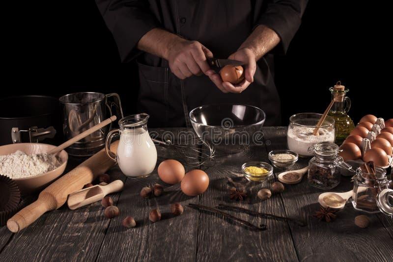 Ο αρσενικός αρχιμάγειρας προετοιμάζει το ευώδες κέικ με τα μέρη των καρυκευμάτων Σκοτεινό κλειδί στοκ εικόνες με δικαίωμα ελεύθερης χρήσης
