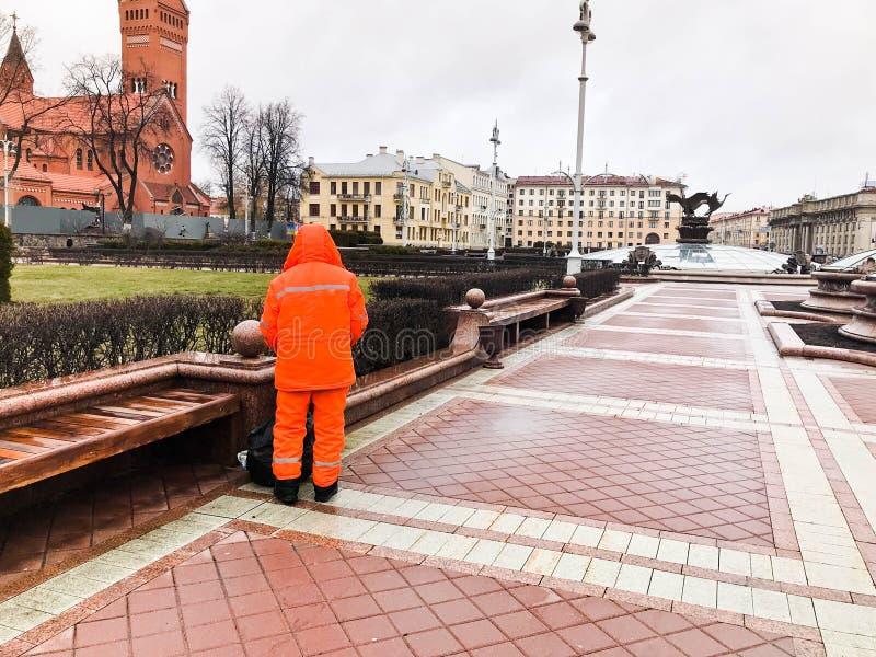 Ο αρσενικός εργαζόμενος καθαριστής στις πορτοκαλιές φόρμες που φορούν τα ενδύματα τηβέννων που λειτουργούν καθαρίζει τις οδούς τη στοκ φωτογραφία με δικαίωμα ελεύθερης χρήσης