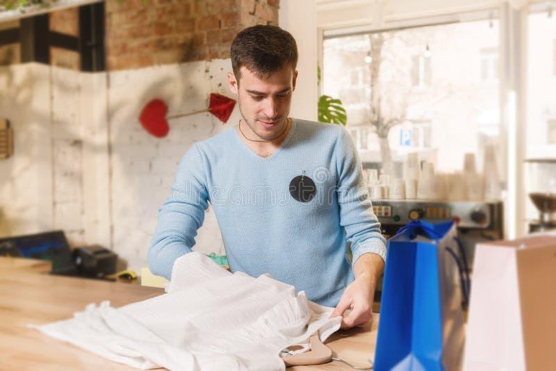 Ο αρσενικός σύμβουλος τακτοποιεί την μπλούζα στο κατάστημα ενδυμάτων στοκ εικόνα με δικαίωμα ελεύθερης χρήσης