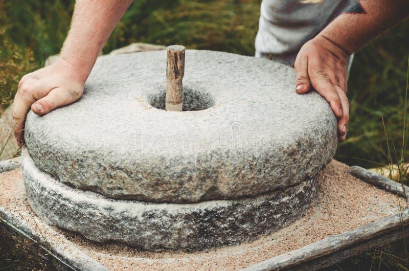 Ο αρχαίος μύλος χεριών πετρών Quern με το σιτάρι Το άτομο αλέθει το σιτάρι στο αλεύρι με τη βοήθεια millstone Άτομα ` s στοκ εικόνα