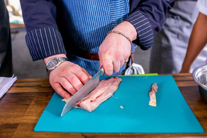 Ο αρχιμάγειρας επιδεικνύει πώς να κόψει τα ψάρια Κύρια κατηγορία στην κουζίνα Η διαδικασία Έννοια με τα ανθρώπινα ίχνη σεμινάριο  στοκ φωτογραφίες με δικαίωμα ελεύθερης χρήσης