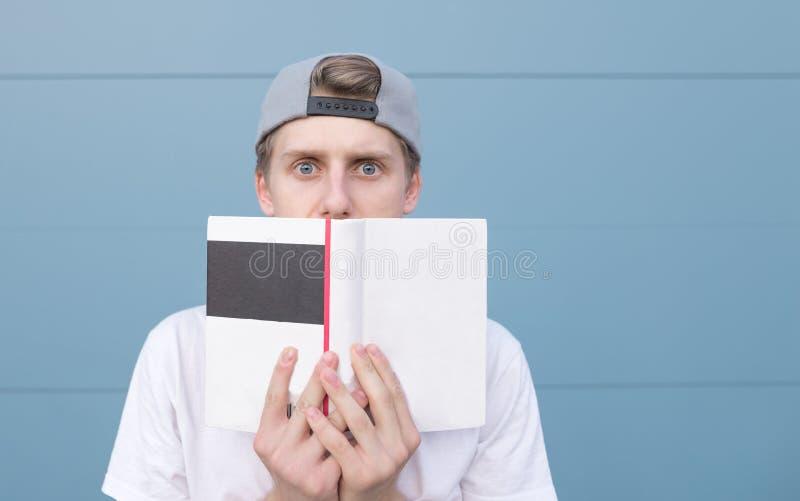 Ο αστείος νεαρός άνδρας με το έκπληκτο βλέμμα έκρυψε πίσω από ένα βιβλίο στο υπόβαθρο ενός μπλε τοίχου στοκ εικόνα