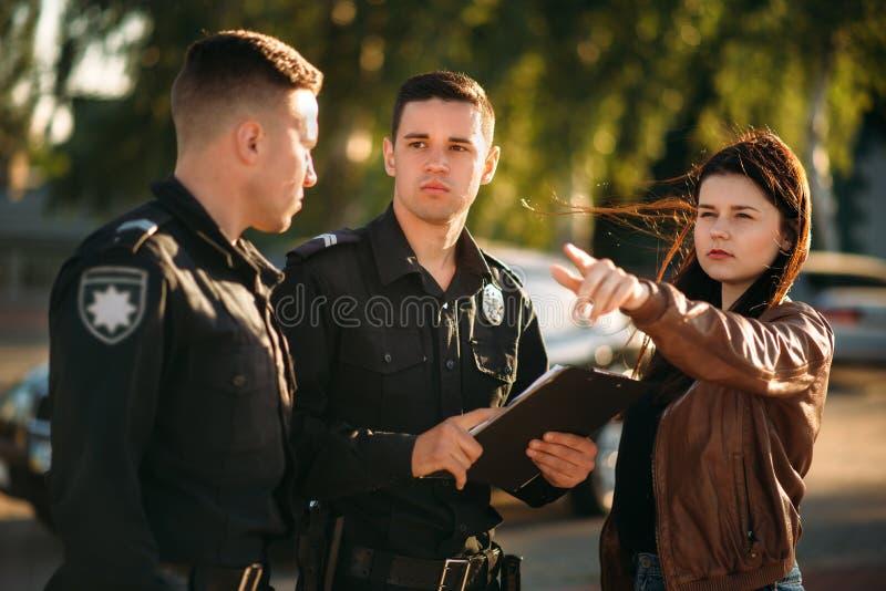 Ο αστυνομικός γράφει την κατάθεση του θηλυκού οδηγού στοκ εικόνες με δικαίωμα ελεύθερης χρήσης