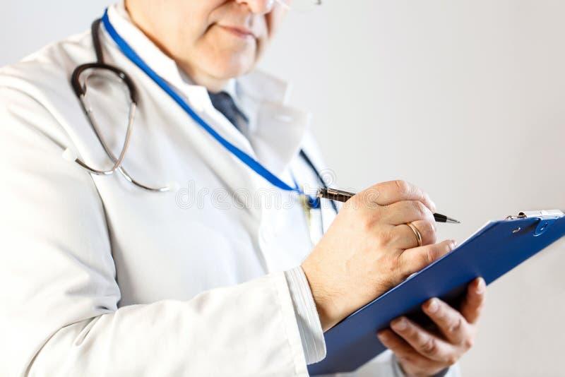 Ο γιατρός κάνει μια είσοδο στην υπομονετική κάρτα στοκ εικόνες