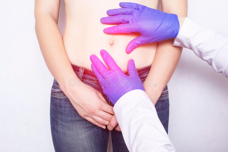 Ο γιατρός διευθύνει μια ιατρική εξέταση του κοριτσιού του ασθενή του οποίου κοιλιακός πόνος, καλωδιακή κήλη της κοιλίας στοκ εικόνες