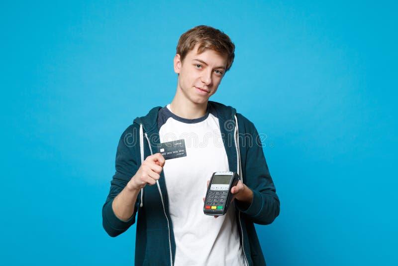 Ο ελκυστικός νεαρός άνδρας που κρατά το ασύρματο σύγχρονο τερματικό πληρωμής τραπεζών στη διαδικασία, αποκτά τις πληρωμές με πιστ στοκ φωτογραφίες με δικαίωμα ελεύθερης χρήσης