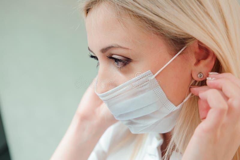 Ο ενήλικος οδοντίατρος βάζει μια προστατευτική μάσκα στο στόμα της στοκ εικόνα με δικαίωμα ελεύθερης χρήσης