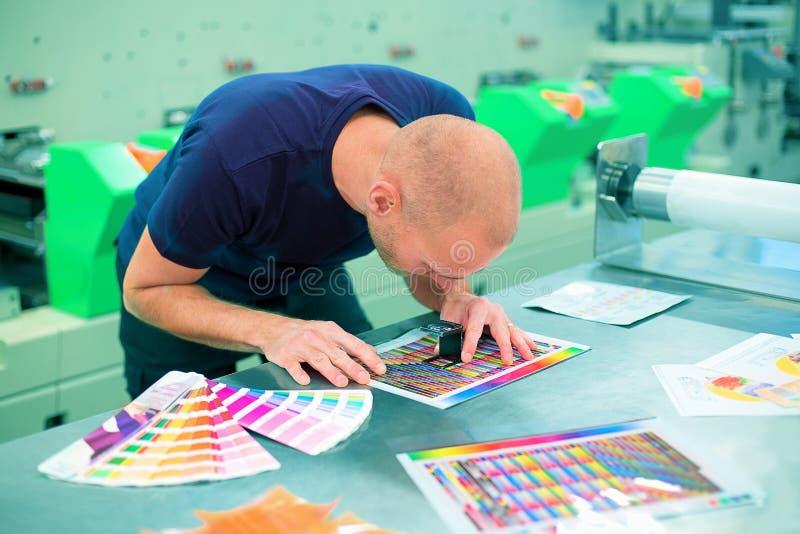 Ο εργαζόμενος σε μια εκτύπωση και ένα κέντρο Τύπου χρησιμοποιεί μια ενίσχυση - γυαλί για να ελέγξει την ποιότητα τυπωμένων υλών Σ στοκ φωτογραφία με δικαίωμα ελεύθερης χρήσης