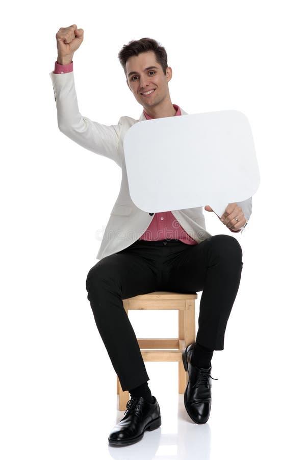 Ο ευτυχής νέος καθισμένος επιχειρηματίας που κρατά μια λεκτική φυσαλίδα γιορτάζει την επιτυχία στοκ φωτογραφία με δικαίωμα ελεύθερης χρήσης