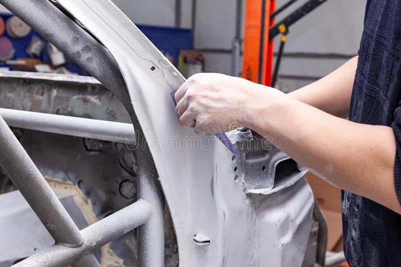 Ο επισκευαστής σωμάτων αλέθει το πλαίσιο του άσπρου αυτοκινήτου με το πορφυρό έγγραφο σμυρίδων σε προετοιμασία για τη ζωγραφική μ στοκ φωτογραφίες με δικαίωμα ελεύθερης χρήσης