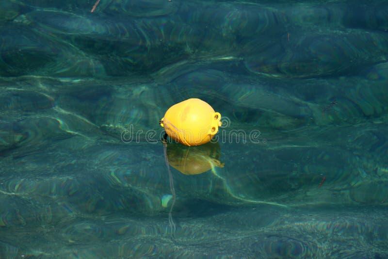 Ο κίτρινος πλαστικός σημαντήρας που επιπλέει στην ήρεμη σαφή θάλασσα με τους ορατούς βράχους και το δεμένο σχοινί σύνδεσε με το κ στοκ εικόνες με δικαίωμα ελεύθερης χρήσης