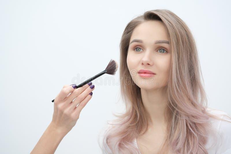 Ο καλλιτέχνης σύνθεσης κάνει makeup το όμορφο ξανθό κορίτσι σε ένα άσπρο υπόβαθρο Χέρια κινηματογραφήσεων σε πρώτο πλάνο με τη βο στοκ φωτογραφία με δικαίωμα ελεύθερης χρήσης