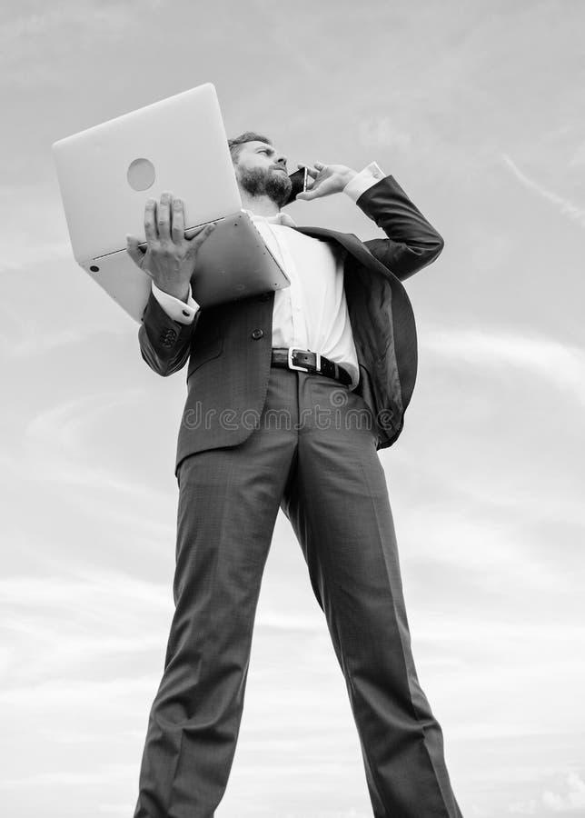 Ο καλλωπισμένος επιχειρηματίας ατόμων καλά κρατά το lap-top ενώ μιλήστε το υπόβαθρο τηλεφωνικού μπλε ουρανού Σύγχρονη τεχνολογία  στοκ φωτογραφία