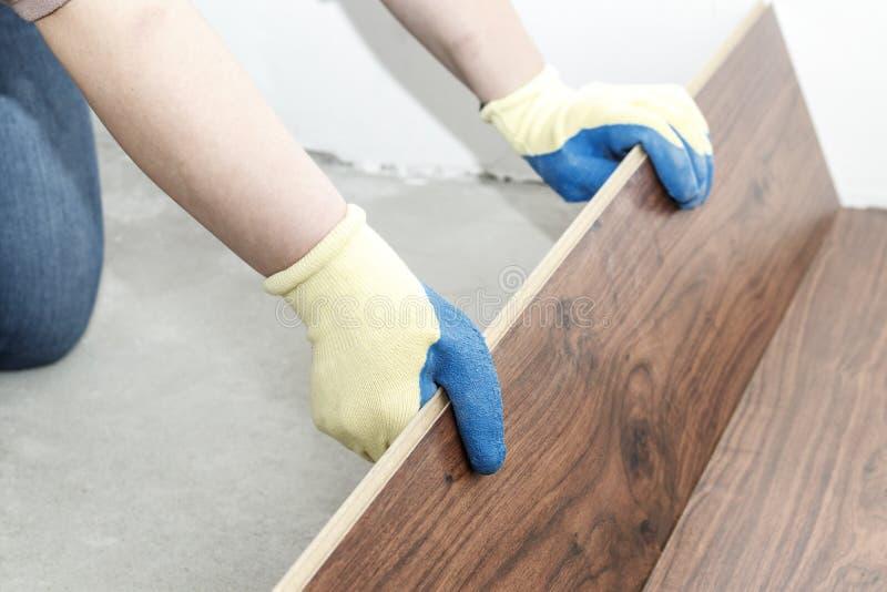 ο κύριος στα μπλε γάντια κάνει την τοποθέτηση floorboard υπάρχει ένα επίπεδο και λαστιχένιο σφυρί στοκ φωτογραφία με δικαίωμα ελεύθερης χρήσης
