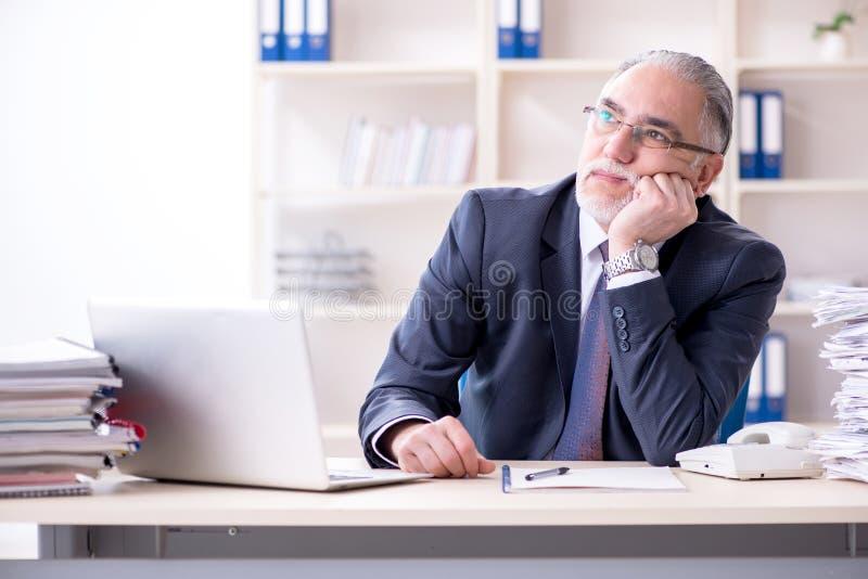 Ο λευκός γενειοφόρος παλαιός υπάλληλος επιχειρηματιών δυστυχισμένος με την υπερβολική εργασία στοκ εικόνες
