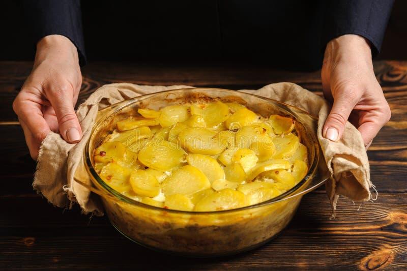 Ο μάγειρας κρατά casserole πατατών με τα χέρια του στοκ εικόνες με δικαίωμα ελεύθερης χρήσης