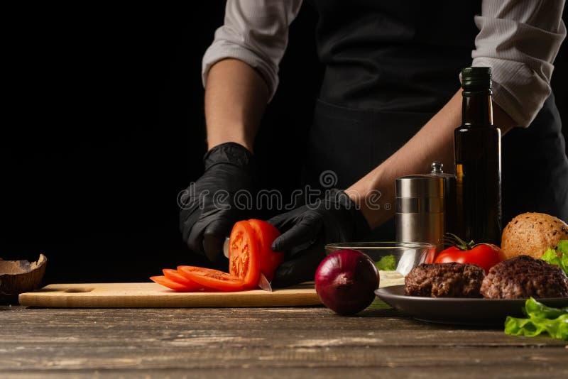 Ο μάγειρας κόβει μια φρέσκια ντομάτα για να κάνει burger, ένα χάμπουργκερ Σε ένα υπόβαθρο με τα συστατικά Εύγευστος και γρήγορο φ στοκ εικόνες