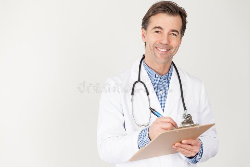 Ο μέσος ηλικίας γιατρός με ένα στηθοσκόπιο γύρω από το λαιμό και την εκμετάλλευσή του ένα αρχείο των ασθενών καταγράφει στα χέρια στοκ εικόνα με δικαίωμα ελεύθερης χρήσης