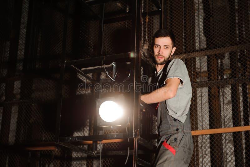 Ο μηχανικός φωτισμού ρυθμίζει τα φω'τα στη σκηνή κοντά στις σκηνές στοκ φωτογραφία με δικαίωμα ελεύθερης χρήσης