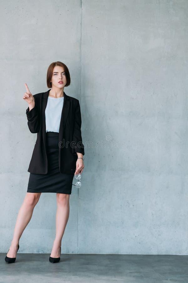 Ο νέος βέβαιος επιχειρησιακός συνάδελφος γυναικών κοιτάζει στοκ φωτογραφία