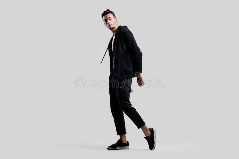 Ο νέος όμορφος χορευτής έντυσε στα μαύρα εσώρουχα και μια μπλούζα στάσεις στις γυμνές κορμών στο άσπρο υπόβαθρο στοκ φωτογραφία με δικαίωμα ελεύθερης χρήσης