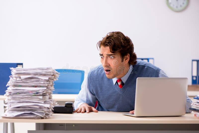 Ο νέος όμορφος υπάλληλος δυστυχισμένος με την υπερβολική εργασία στοκ εικόνες με δικαίωμα ελεύθερης χρήσης