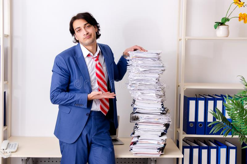 Ο νέος υπάλληλος επιχειρηματιών δυστυχισμένος με την υπερβολική εργασία στοκ εικόνες
