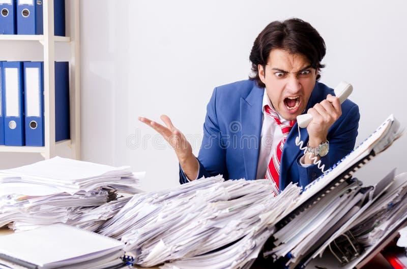 Ο νέος υπάλληλος επιχειρηματιών δυστυχισμένος με την υπερβολική εργασία στοκ εικόνα