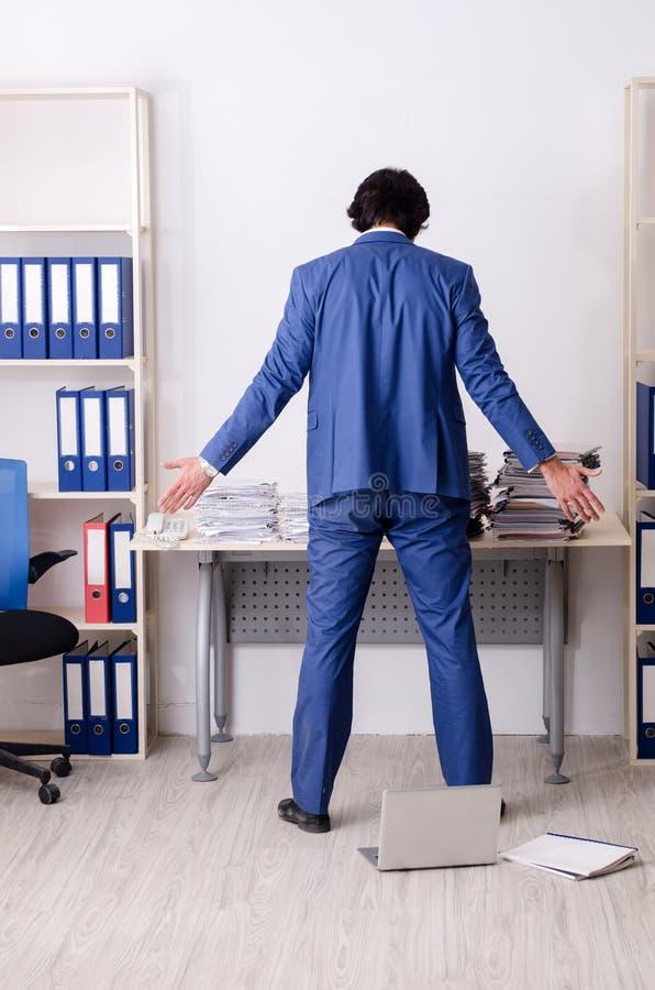Ο νέος υπάλληλος επιχειρηματιών δυστυχισμένος με την υπερβολική εργασία στοκ φωτογραφία