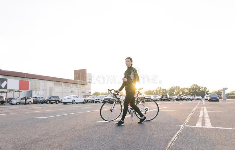 Ο νέος ποδηλάτης περπατά με ένα άσπρο ποδήλατο στο χώρο στάθμευσης στα πλαίσια του ηλιοβασιλέματος στοκ εικόνα