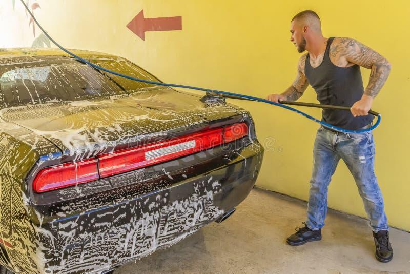 Ο νεαρός άνδρας σαπουνίζει επάνω το μαύρο αυτοκίνητό του στοκ φωτογραφία