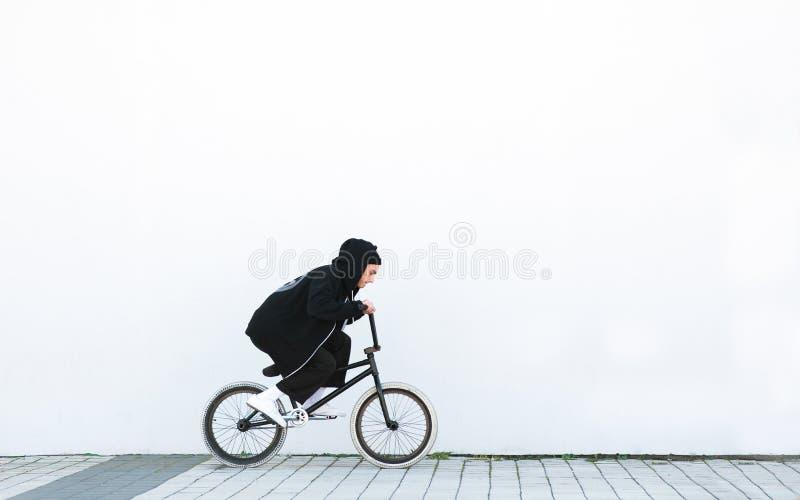 Ο νεαρός άνδρας σε έναν μαύρο περιστασιακό ιματισμό οδηγά ένα ποδήλατο bmx στο υπόβαθρο ενός άσπρου τοίχου στοκ φωτογραφία