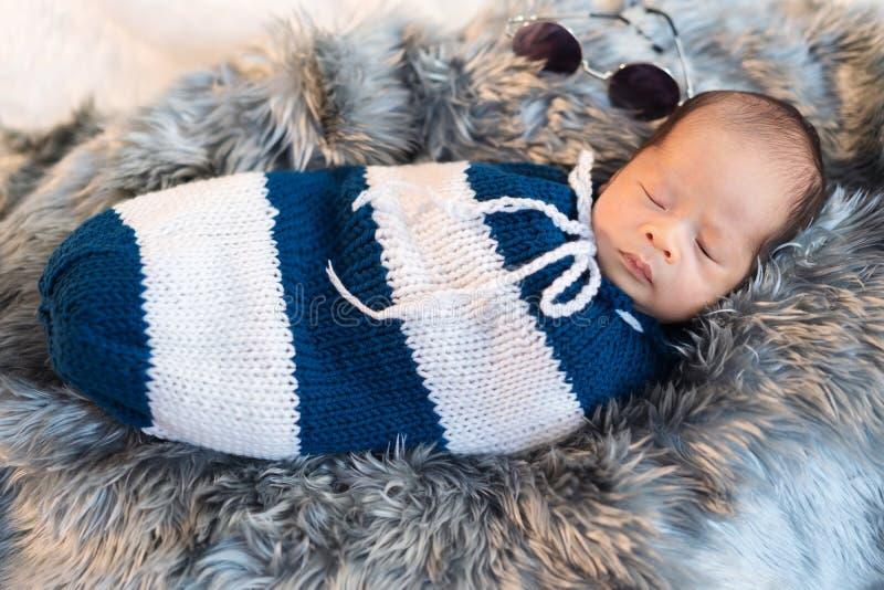 Ο νεογέννητος ύπνος αγοράκι και πλέκει το περικάλυμμα στο κρεβάτι στοκ εικόνες