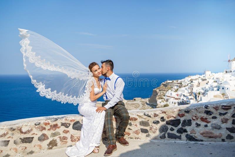 Ο νεόνυμφος φιλά τη νύφη, κυματισμοί πέπλων στον αέρα στοκ εικόνα με δικαίωμα ελεύθερης χρήσης