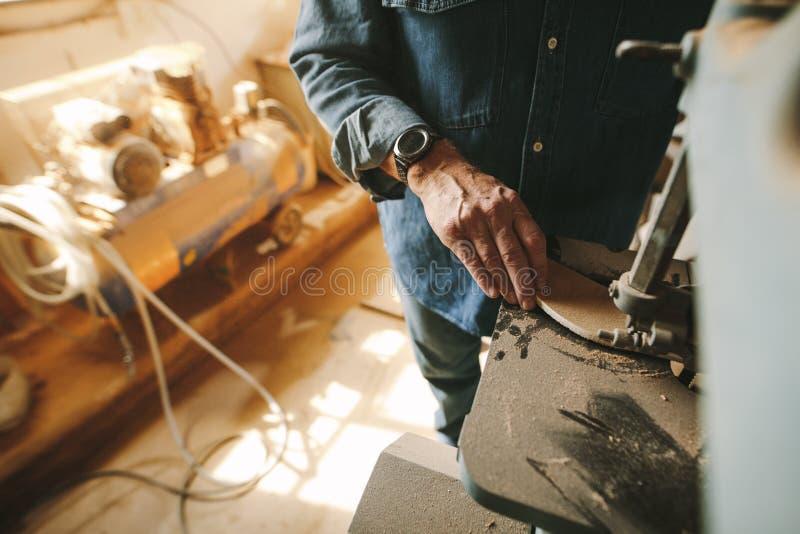 Ο ξυλουργός κόβει και διαμορφώνει το ξύλινο χρησιμοποιώντας πριόνι ζωνών στοκ φωτογραφία