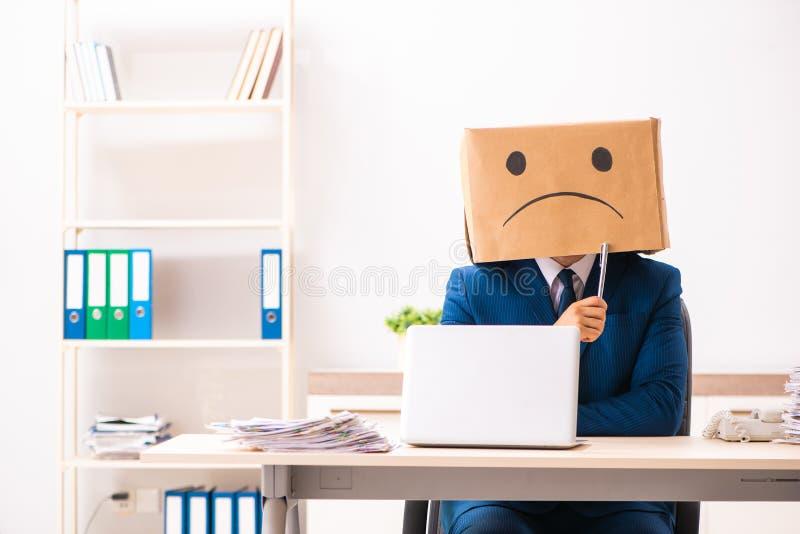 Ο δυστυχισμένος υπάλληλος ατόμων με το κιβώτιο αντί του κεφαλιού του στοκ εικόνες