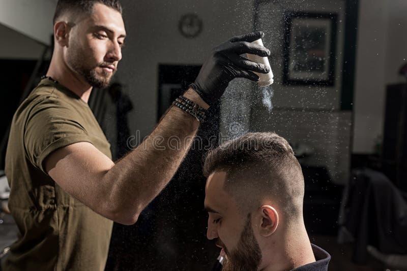 Ο όμορφος κουρέας καθορίζει τον προσδιορισμό του βάναυσου νεαρού άνδρα με ένα ξηρό styler σε ένα barbershop στοκ εικόνες