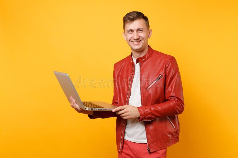 Ο όμορφος νεαρός άνδρας διασκέδασης μόδας πορτρέτου στο κόκκινο σακάκι δέρματος, μπλούζα που χρησιμοποιεί την ταμπλέτα PC lap-top στοκ εικόνες με δικαίωμα ελεύθερης χρήσης