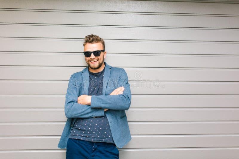 Ο όμορφος τύπος θέτει στο γκρίζο υπόβαθρο τοίχων Φορά το γκρίζο σακάκι, μπλούζα, τζιν, γυαλιά ηλίου Χαμογελά στοκ εικόνες