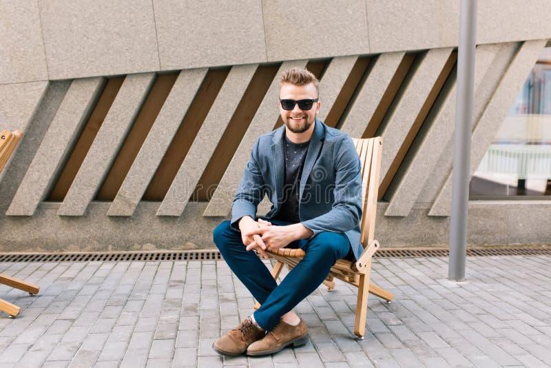 Ο όμορφος τύπος κάθεται στην καρέκλα υπαίθρια στο υπόβαθρο καφέδων Φορά το γκρίζο σακάκι, τζιν, καφετιά παπούτσια, γυαλιά ηλίου Ε στοκ φωτογραφία με δικαίωμα ελεύθερης χρήσης