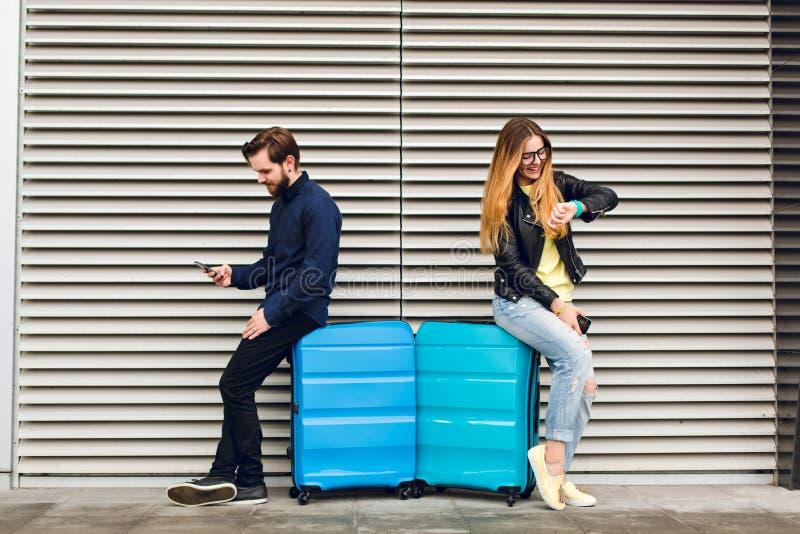 Ο όμορφος τύπος με τη γενειάδα έκλινε στη βαλίτσα στο γκρίζο ριγωτό υπόβαθρο και τη δακτυλογράφηση στο τηλέφωνο μακρύς όμορφος τρ στοκ φωτογραφία με δικαίωμα ελεύθερης χρήσης