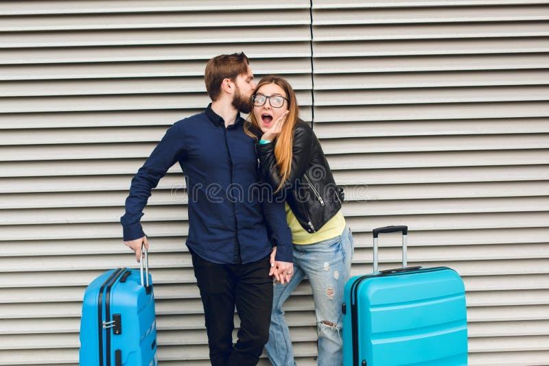 Ο όμορφος τύπος με τη γενειάδα στο μαύρο πουκάμισο φιλά το κορίτσι με μακρυμάλλη στο γκρίζο ριγωτό υπόβαθρο Φορά τα γυαλιά στοκ εικόνες με δικαίωμα ελεύθερης χρήσης