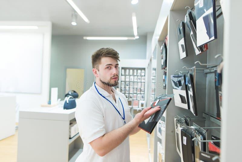Ο σύμβουλος του καταστήματος τεχνολογίας είναι στο τμήμα εξαρτημάτων συσκευών στοκ φωτογραφία
