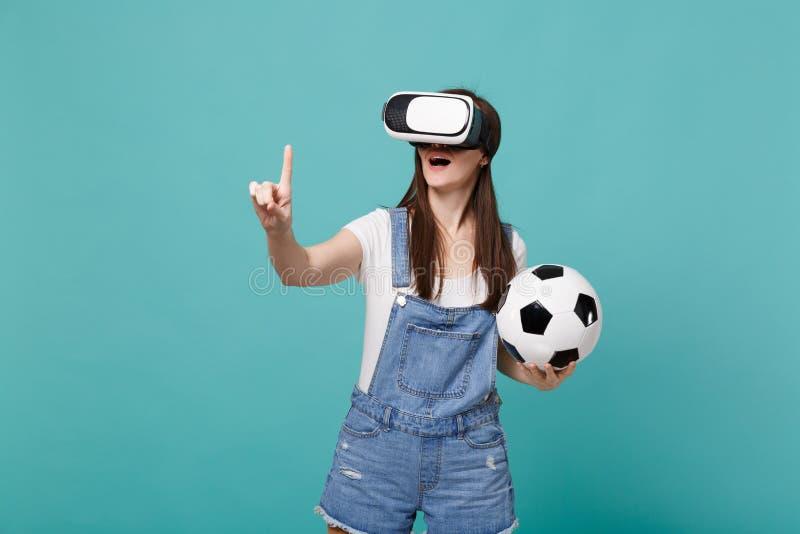 Ο συγκινημένος οπαδός ποδοσφαίρου νέων κοριτσιών που κοιτάζει στην παίζοντας αφή σφαιρών ποδοσφαίρου εκμετάλλευσης κασκών κάτι σα στοκ εικόνα
