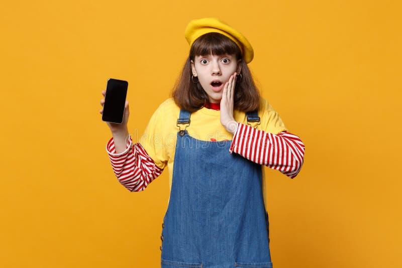 Ο συγκλονισμένος έφηβος κοριτσιών γαλλικό beret έβαλε το χέρι στο πρόσωπο, που κρατά το κινητό τηλέφωνο με την κενή κενή οθόνη πο στοκ φωτογραφίες με δικαίωμα ελεύθερης χρήσης